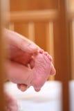 De voet van de baby en de hand van zijn vader Stock Foto's