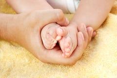 De voet van de baby in vaderhanden Stock Afbeeldingen