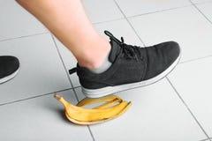 De voet van de mens glijdt op de schil van een heerlijke, verse, tropische heldere gele banaan op de vloer Veiligheid en achteloo royalty-vrije stock foto