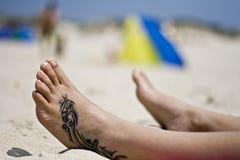 De voet van de tatoegering in het zand royalty-vrije stock fotografie