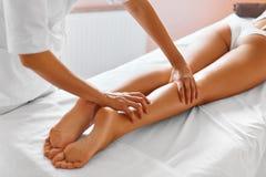 De voet van de vrouw in het water Close-up die van vrouw kuuroordbehandeling krijgen Benenmassage Stock Afbeeldingen