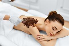 De voet van de vrouw in het water De behandeling van de kuuroordschoonheid Kosmetisch masker De zorg van de huid Stock Afbeelding