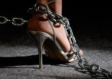 De voet van de vrouw in kettingen stock afbeelding