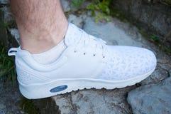 De voet van een mens in witte tennisschoenen bevindt zich op steenstappen in de zomer stock foto's