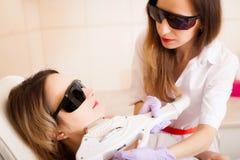 De voet van de vrouw in het water Close-up van de Behandeling van Schoonheidsspecialistgiving laser epilation aan Jong Vrouwengez royalty-vrije stock fotografie