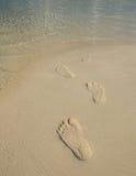 De voetaf:drukken van de toerist op strand Stock Afbeelding