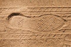 De voetafdruk betreedt schoenen en banden op het zand royalty-vrije stock afbeelding