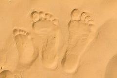De voetafdrukken van de familie op zand stock afbeelding
