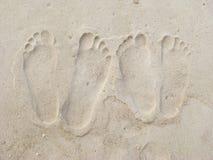 De voetafdrukken van het paar in het zand Stock Foto