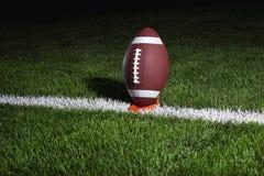 De voetbal van de universiteit op T-stuk bij nacht klaar voor schop van Stock Afbeeldingen