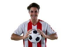 De voetbal van de voetbalsterholding met beide handen Stock Afbeeldingen