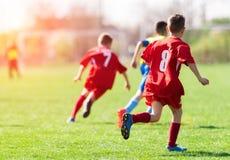 De voetbal van het jonge geitjesvoetbal - de gelijke van kinderenspelers op voetbalgebied stock afbeelding