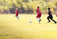 De voetbal van het jonge geitjesvoetbal - de gelijke van kinderenspelers op voetbalgebied royalty-vrije stock afbeelding