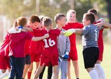 De voetbal van het jonge geitjesvoetbal - kinderenspelers die na victo vieren stock foto's