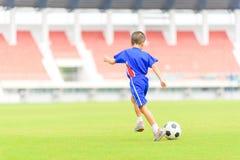 De voetbal van het jongensspel Stock Foto's