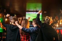 De voetbal van vriendenhorloges op TV in een sportbar Stock Foto's