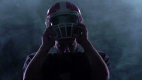 De voetbal zet de helm op het hoofd in de rook Langzame Motie stock video