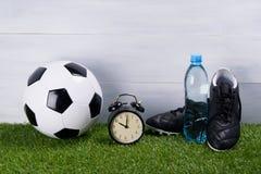 De voetbalbal, een fles water, de zwarte laarzen en een wekker bevinden zich op het gras, op een grijze achtergrond stock afbeelding