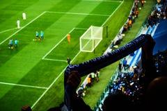 De voetbalfans juichen hun de scoredoel van het voetbalteam met vlaggen, banners en sjaals bij het stadion toe Langzaam verdwenen royalty-vrije stock afbeelding
