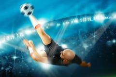 De voetballer in actie schiet het balomgekeerde Stock Foto
