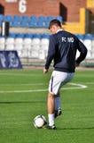 De voetballer speelt op het gebied met de bal Stock Afbeeldingen