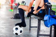 De voetballer zit en zet zwarte sportsok met voetbalbal stock foto's