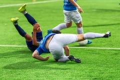 De voetballers spelen slechte voetbal Zij ontbreken tijdens de Wereldbeker Een voetballer wordt verwond tijdens een schending van Stock Afbeelding