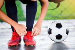 De voetballers zitten en bindende sportschoenveters met voetbalbal stock afbeeldingen