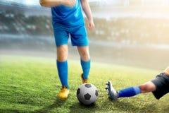 De voetbalstervrouw pakt de bal van haar tegenstander aan royalty-vrije stock afbeeldingen
