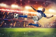 De voetbalstriker raakt de bal met een acrobatische schop stock foto's