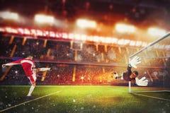 De voetbalstriker raakt de bal met genoeg bevoegdheid om op brand te gaan stock foto
