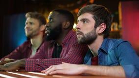 De voetbalventilators die op spel in bar letten, mannelijke vrienden die met team worden teleurgesteld verliezen stock footage