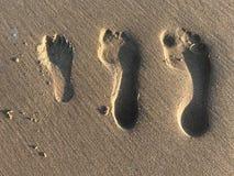 De voetdrukken van de familie in het zand stock afbeelding