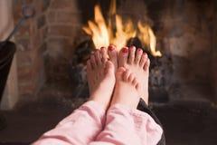 De voeten die van de moeder en van de dochter bij een open haard verwarmen royalty-vrije stock afbeeldingen