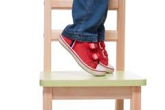 De voeten die van het kind zich op de kleine stoel op tiptoe bevinden Stock Foto's