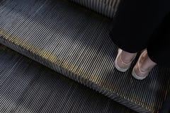 De voeten die van het wijfje zich op die een trap bevinden van de metaalroltrap hierboven wordt geschoten van stock afbeelding