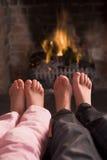 De voeten die van kinderen bij een open haard verwarmen Stock Afbeelding