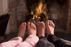 De voeten die van kinderen bij een open haard verwarmen Stock Foto's
