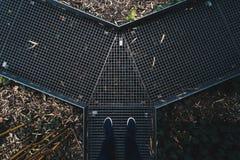 De voeten die van de mens zich op een metaal smalle weg bevinden in een botanische tuin stock afbeelding