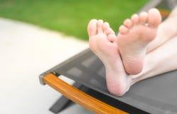 De voeten en de zolen van persoon die sunbed liggen Stock Fotografie