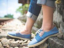 De voeten van de close-upvrouw in blauwe tennisschoenen die door de spoorweg zitten stock fotografie