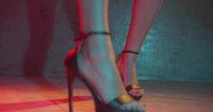 De voeten van de close-upvrouw in hoge hielen die in de studio met neon dansen kleuren licht stock videobeelden
