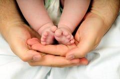 De voeten van de baby in dadshand Stock Afbeeldingen