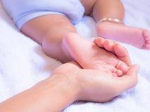 De voeten van de baby in moederhanden Stock Afbeeldingen