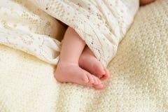 De voeten van de baby sluiten omhoog Benen van een zuigeling stock afbeeldingen