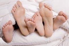 De voeten van de vrouw en van jonge geitjes in bed Stock Foto