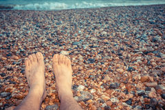 De voeten van een jonge mensenzitting op het strand Stock Foto's