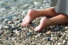 De voeten van een jonge vrouw op het strand Stock Foto's