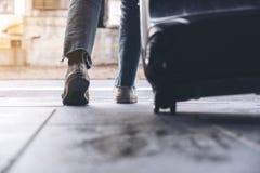 De voeten van een vrouw terwijl in openlucht het reizen van en het slepen van een zwarte bagage in royalty-vrije stock fotografie