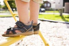 De voeten van het kind in een speelplaats stock afbeeldingen